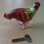 Wind-up Toy - this is chicken is made of tin, and has a simple clockwork mechanism inside it that would be wound with a key. The chicken then hops around and pecks at the floor. It is made from folded thin pieces of tin that have quite sharp edges.